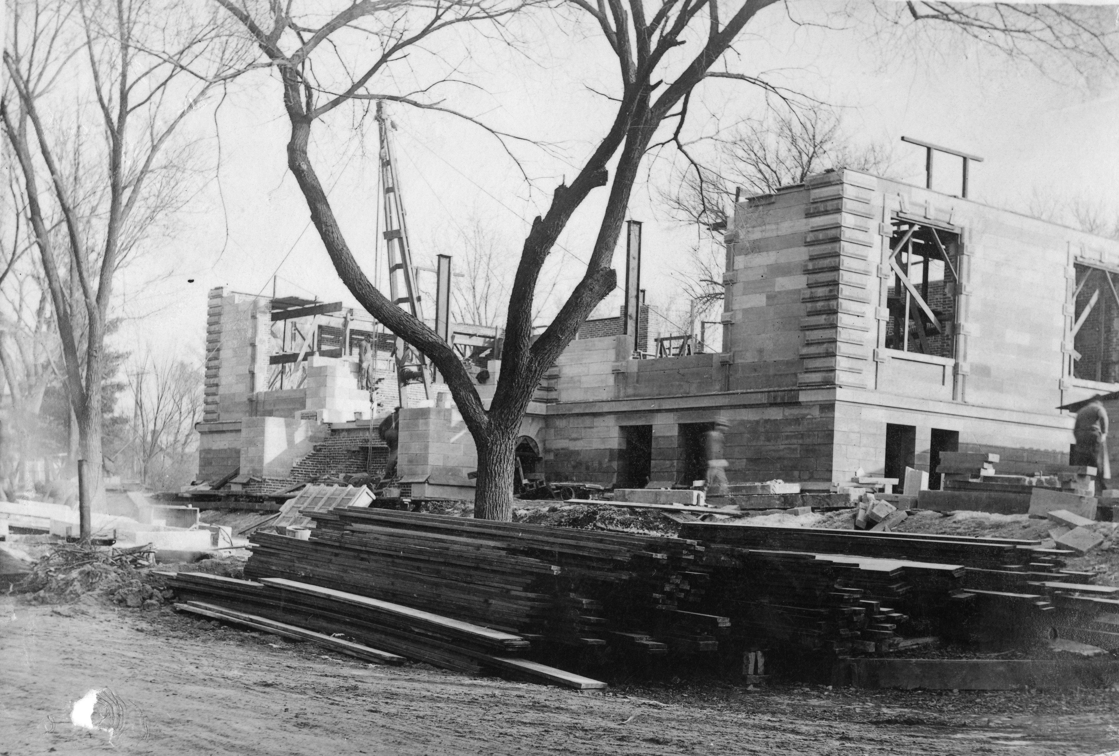 Workers building up the walls, stairs, and windows of the Carnegie building
