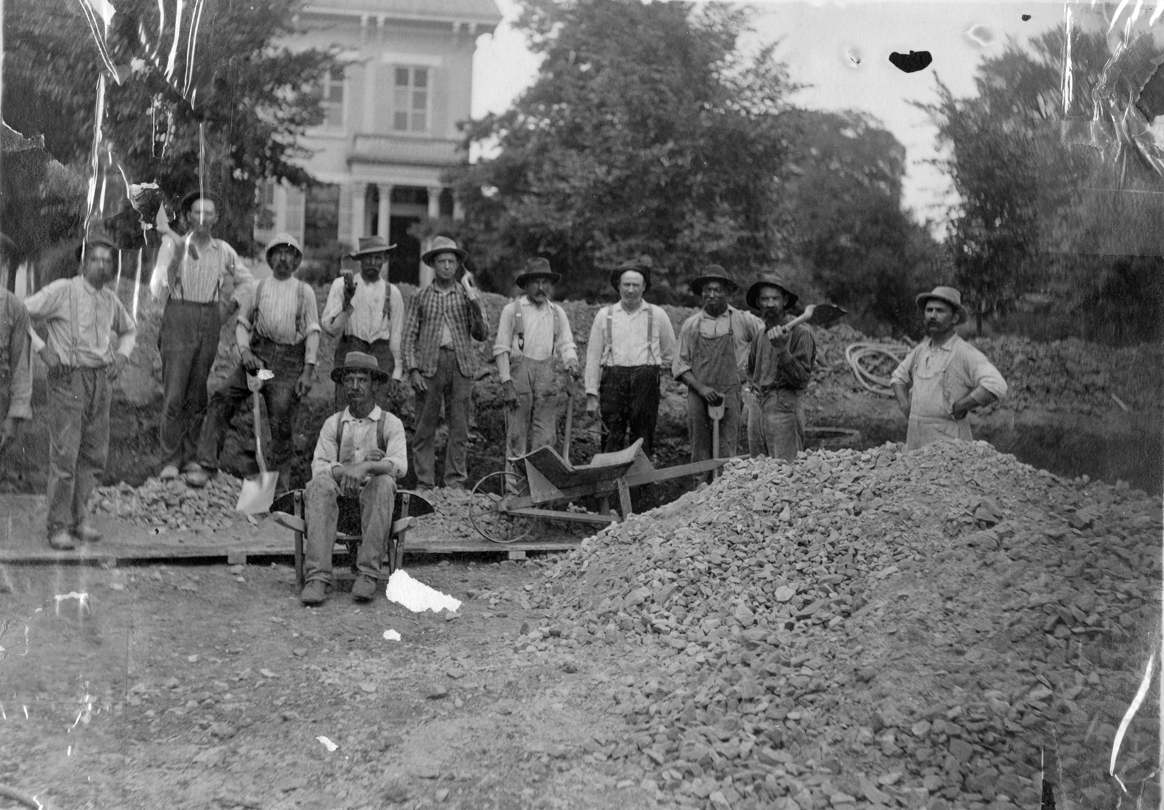 Workers pose in the dug out foundation of the Carnegie building next to a large pile of gravel