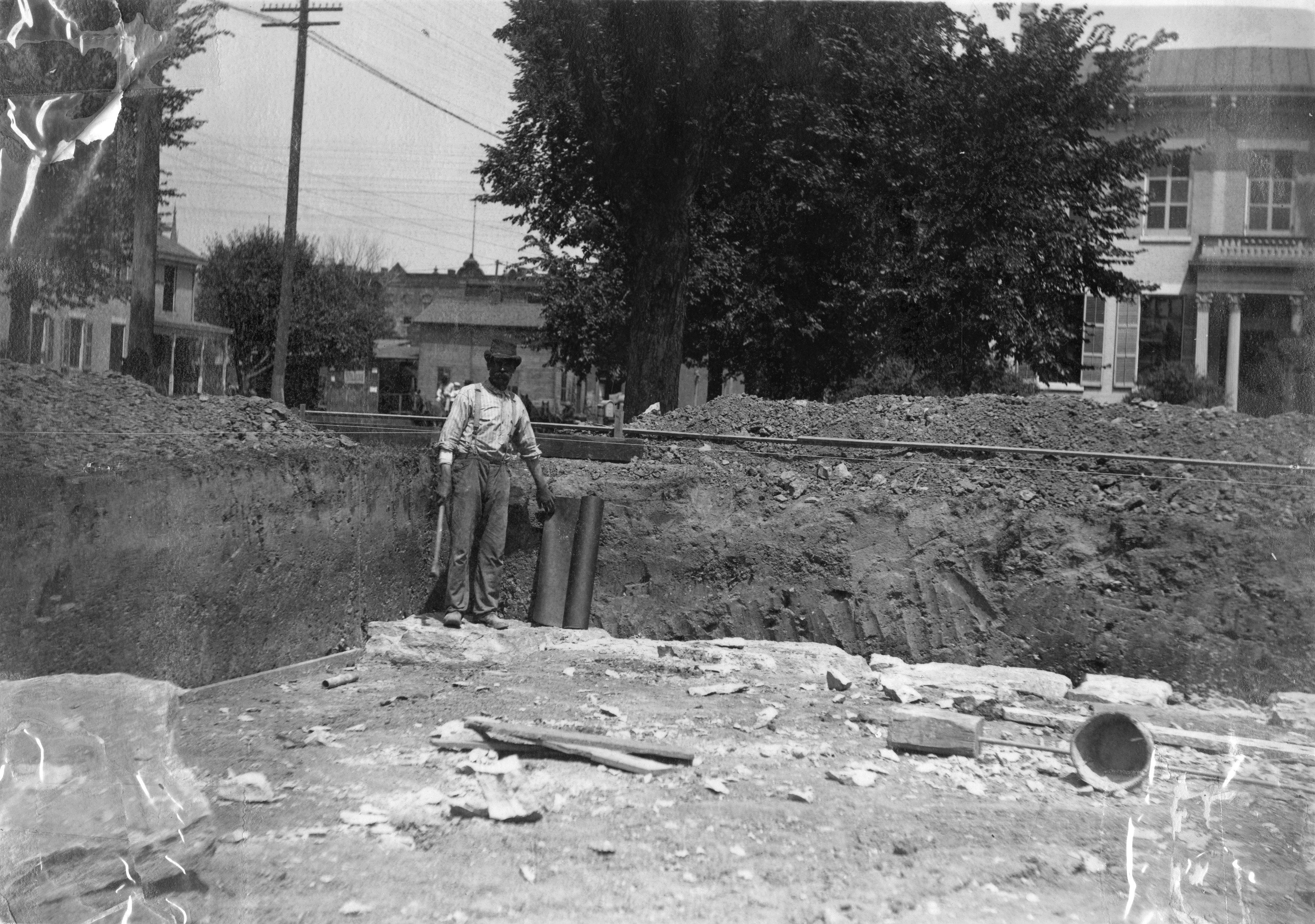 A single worker poses for a photo in the dug out foundation of the Carnegie building