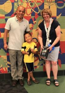 Edward Li is the winner of the Kids Summer Reading Program Grand Pirze, a Kindle Fire. He is pictured with his father, Richard Li, and Vickie Pasicznyk, the Children