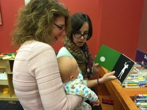 Karen and Morgan read a high-contrast book on baby's first trip to the library.