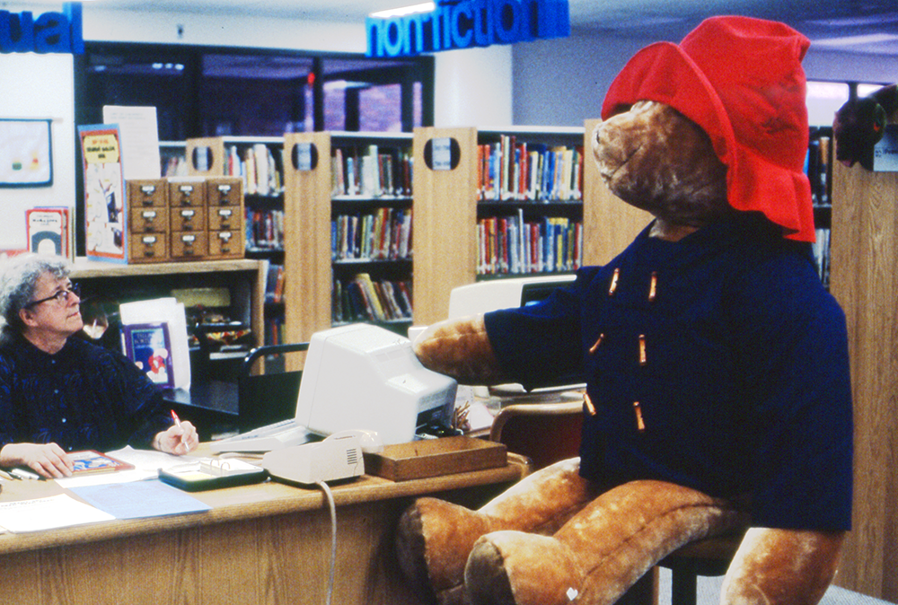 Hazel at desk next to large Paddington Bear