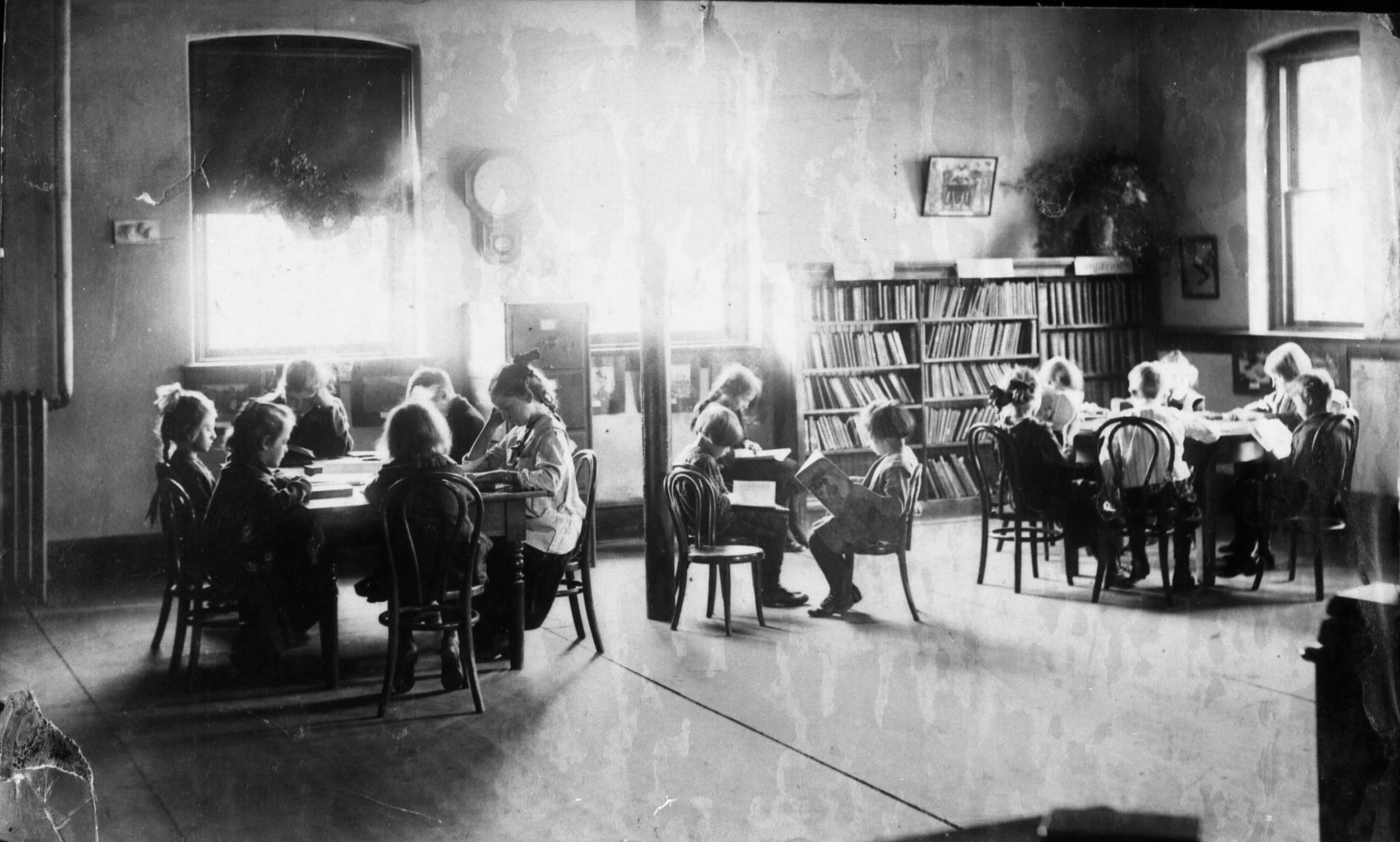 Children sit around tables in the children's room of the Carnegie building