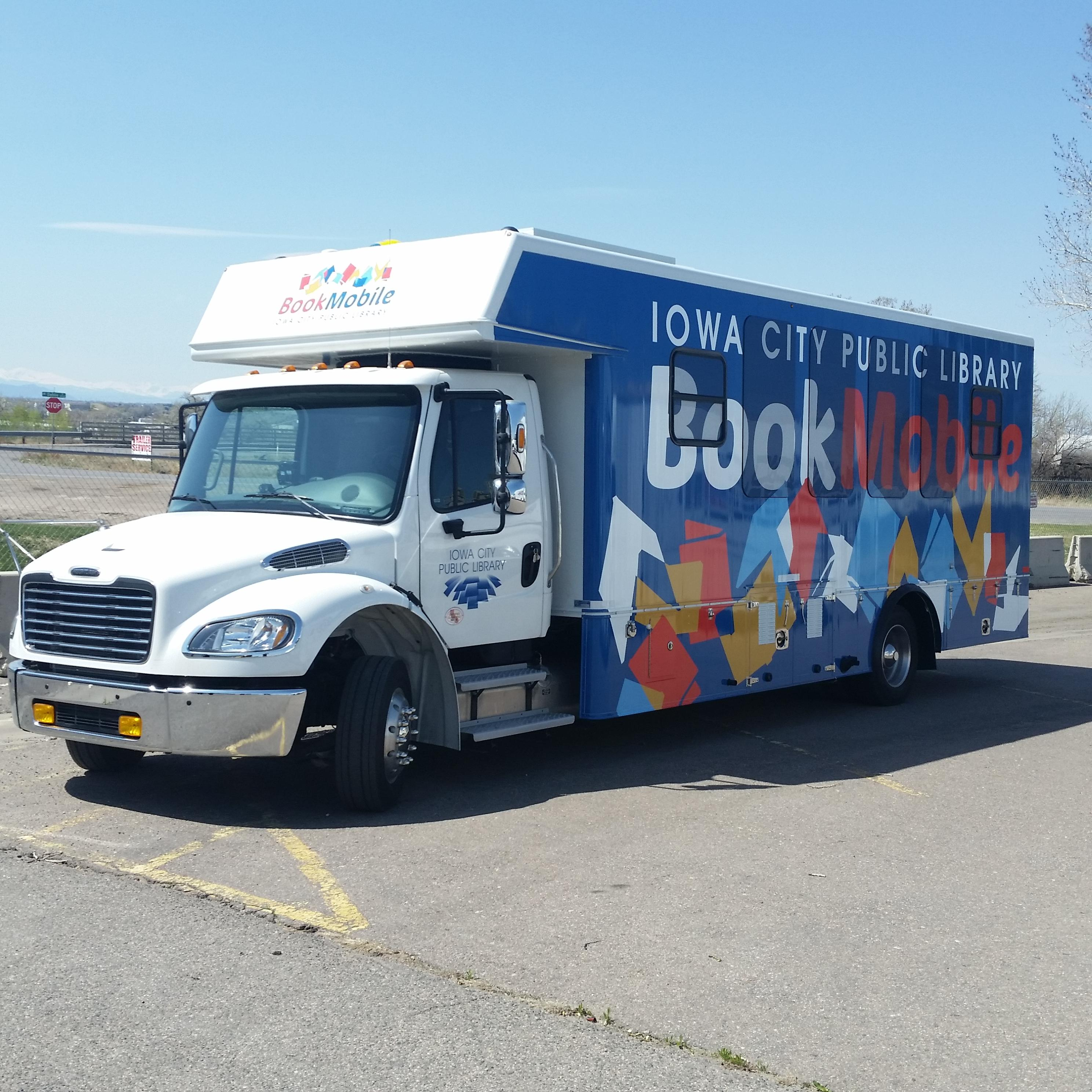 ICPL Bookmobile parked on a concrete lot, with blue sky visible.