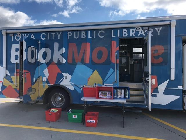 ICPL Bookmobile parked in front of a blue sky, with doors open and bins of books set out for browsing.
